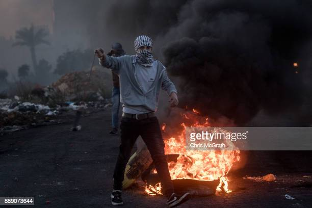 Palestinian protester hurls stones at Israeli border guards during clashes near an Israeli checkpoint on December 9 2017 in Ramallah West Bank...