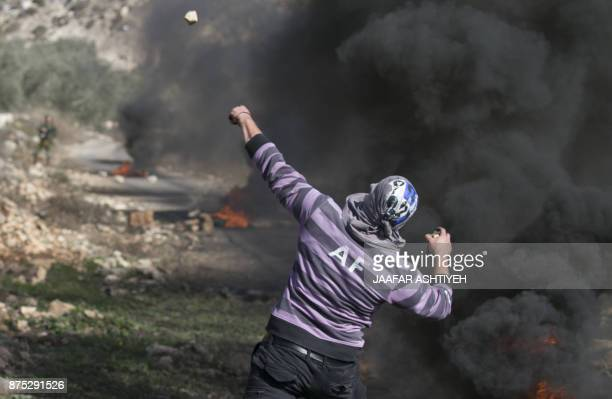 A Palestinian protester hurls stones towards Israeli forces next to burning tyres during clashes that followed a weekly demonstration against the...