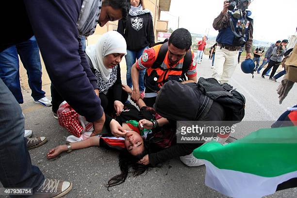 Palestinian protester is assisted as she fainted because of inhalation of tear gas during clashes with Israeli security forces following a...