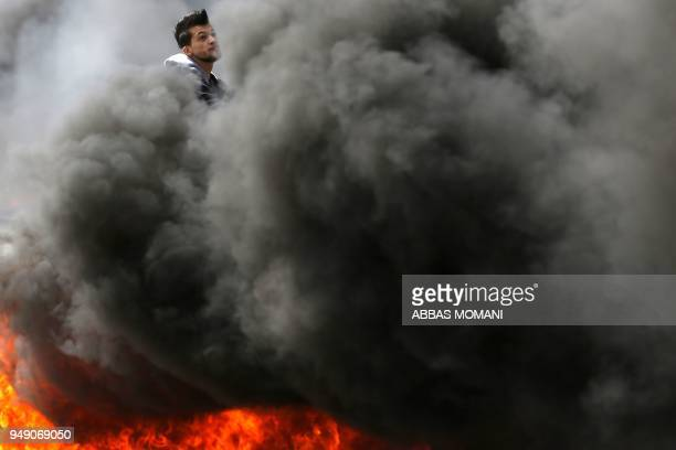 Palestinian protester is seen amidst the smoke from burning tires during clashes with Israeli forces following a demonstration near the Israeli...