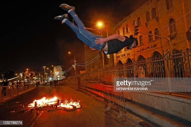 Palestinian protester is seen in midair during a parkour stunt near an Israeli security barrier outside the Damascus Gate in Jerusalem's Old City on...