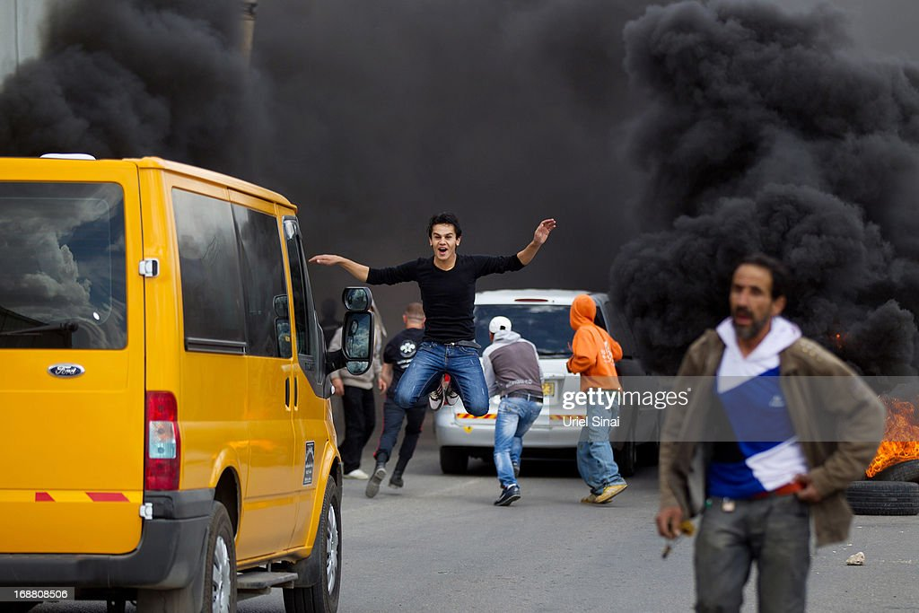 A Palestinian protester jumps as tires burn during clashes with the Israeli army during Nakba day on May 15, 2013 near the Qalandia checkpoint at the outskirts of Ramallah, the West Bank. Palestinians mark Israel's establishment in 1948 with 'Nakba' or 'catastrophe' day on May 15, to remember the thousands of Palestinians who fled or were expelled during the creation of the Jewish state and the subsequent war.