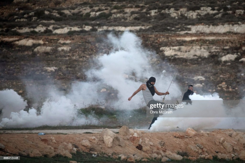 A Palestinian protester kicks away a tear gas cannister during clashes with Israeli border guards near an Israeli checkpoint on December 8, 2017 in Ramallah, West Bank. At least 50 Palestinians have been wounded in clashes between Palestinian protestors and Israeli security forces in the West Bank and the Gaza Strip on Friday after thousands of protestors took to the streets in a second 'Day of Rage' following U.S. President Donald Trump's decision to recognize Jerusalem as Israel's capital on Wednesday.