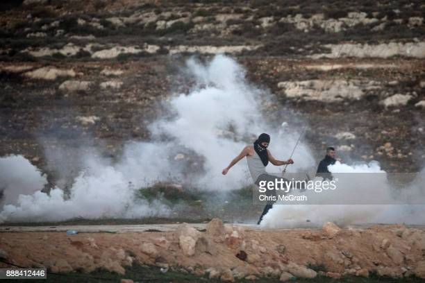 Palestinian protester kicks away a tear gas cannister during clashes with Israeli border guards near an Israeli checkpoint on December 8 2017 in...