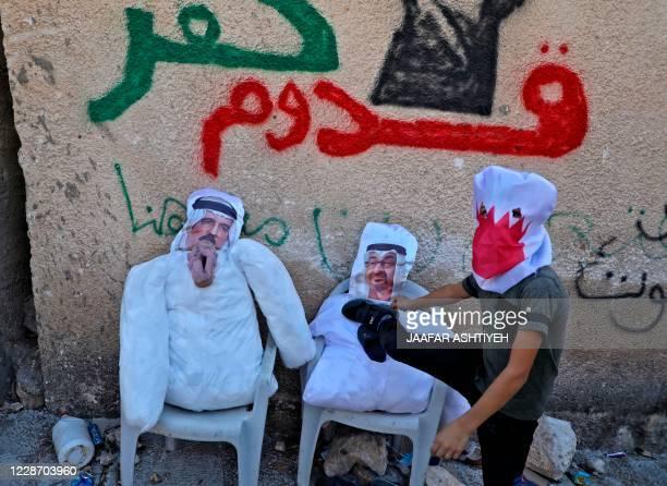 Palestinian protester kicks effigies depicting Bahrain's King Hamad bin Isa Al-Khalifa and Abu Dhabi's Crown Prince Sheikh Mohammed bin Zayed...