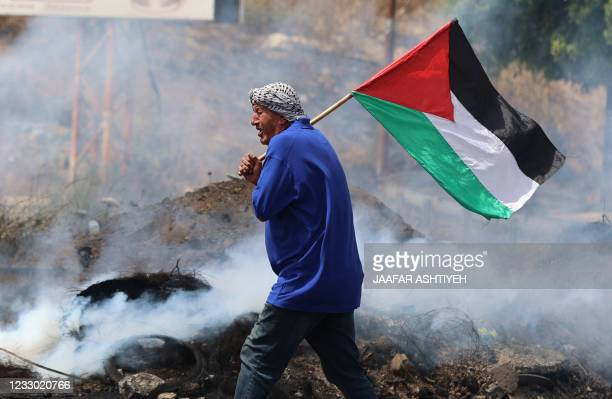 Palestinian protester lifts a national flag amid confrontations with Israeli security forces at the Hawara checkpoint south of Nablus city, in the...