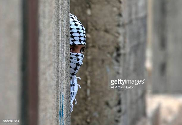 Palestinian protester looks out from a behind wall during clashes with Israeli security forces following a demonstration against the expropriation of...