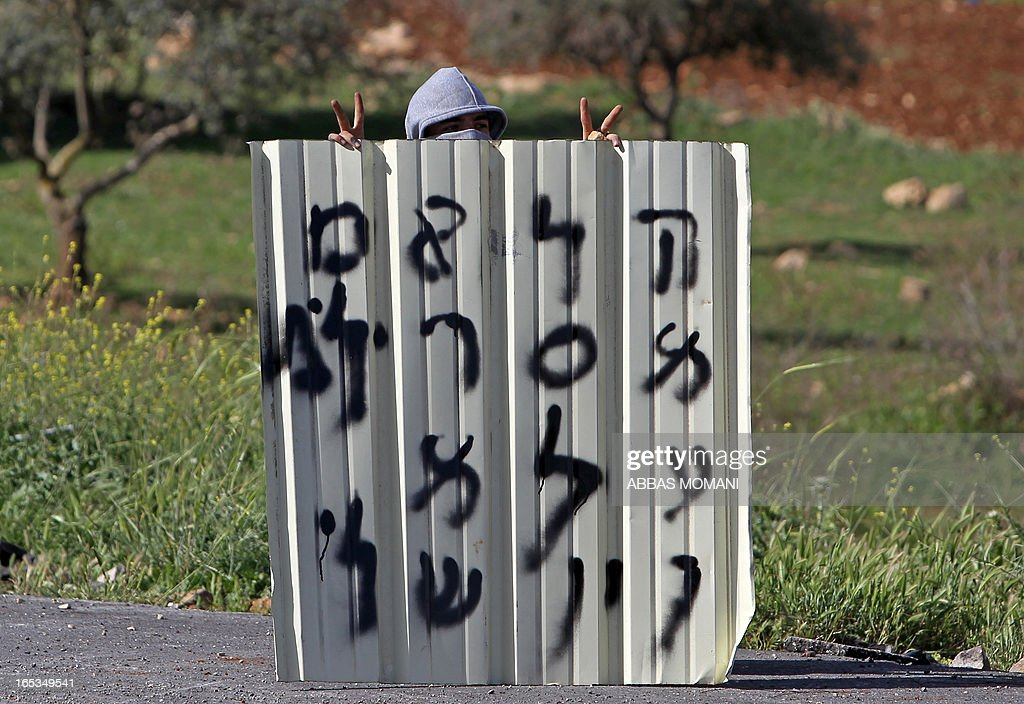 A Palestinian protester makes victory signs behind a makeshift barricade during clashes with Israeli security forces outside Ofer prison near the West Bank city of Ramallah on April 3, 2013 following a protest against the death of a Palestinian prisoner while in detention. Maisara Abu Hamdiyeh, who had served 10 years of a life sentence for attempted murder, died in an Israeli hospital two months after being diagnosed with throat cancer. The Palestinian leadership has accused Israel of medical negligence with news of his death sparking angry clashes.