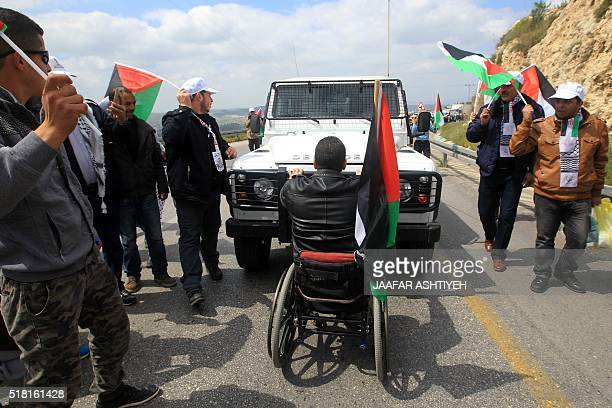 A Palestinian protester on a wheelchair blocks an Israeli jeep during a demonstration to mark Land Day on March 30 2016 in the West Bank village of...