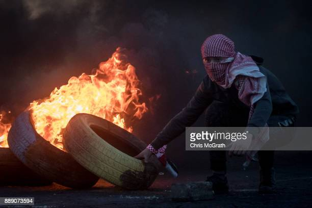 Palestinian protester places a tire on a burning barricade during clashes with Israeli border guards near an Israeli checkpoint on December 9 2017 in...