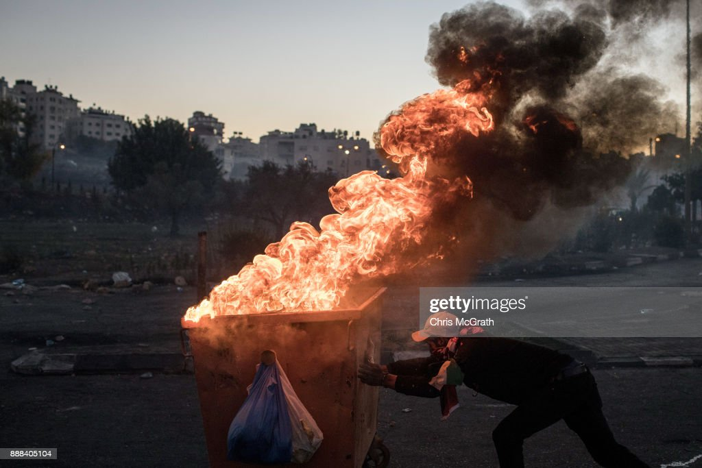 A Palestinian protester pushes a burning dumpster down a street to make a barricade during clashes with Israeli border guards near an Israeli checkpoint on December 8, 2017 in Ramallah, West Bank. At least 50 Palestinians have been wounded in clashes between Palestinian protestors and Israeli security forces in the West Bank and the Gaza Strip on Friday after thousands of protestors took to the streets in a second 'Day of Rage' following U.S. President Donald Trump's decision to recognize Jerusalem as Israel's capital on Wednesday.