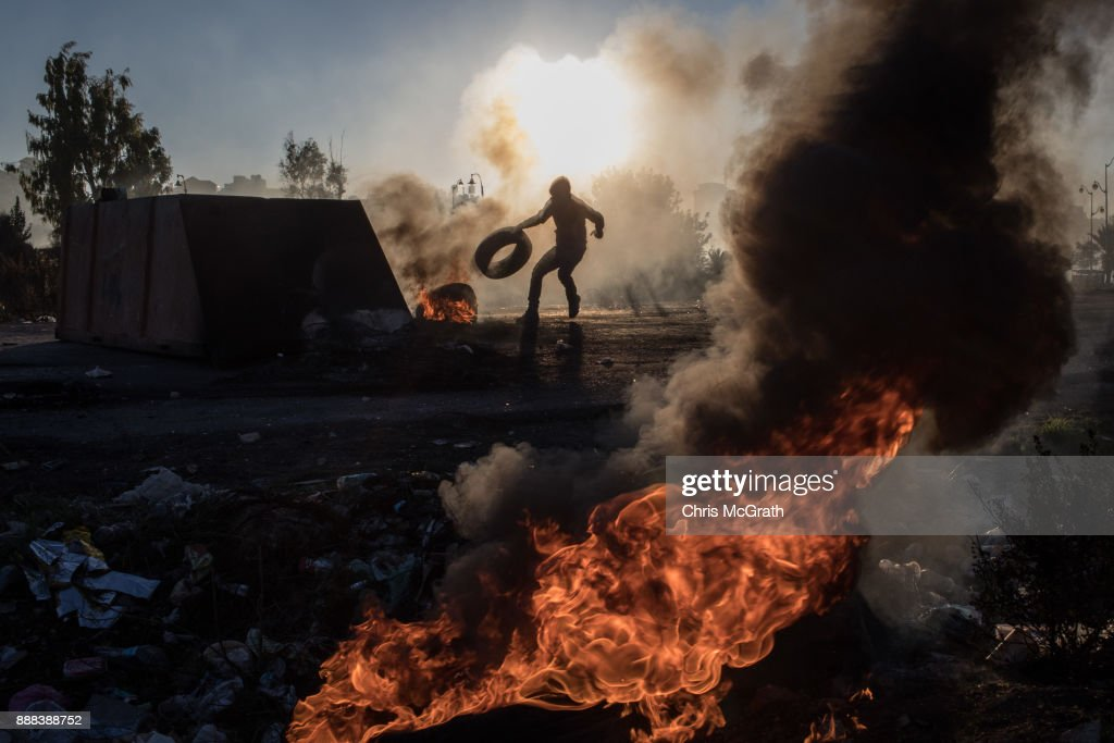 A Palestinian protester pushes a tire onto a fire barricade as they clashed with Israeli border guards near an Israeli checkpoint on December 8, 2017 in Ramallah, West Bank. At least 50 Palestinians have been wounded in clashes between Palestinian protestors and Israeli security forces in the West Bank and the Gaza Strip on Friday after thousands of protestors took to the streets in a second 'Day of Rage' following U.S. President Donald Trump's decision to recognize Jerusalem as Israel's capital on Wednesday.