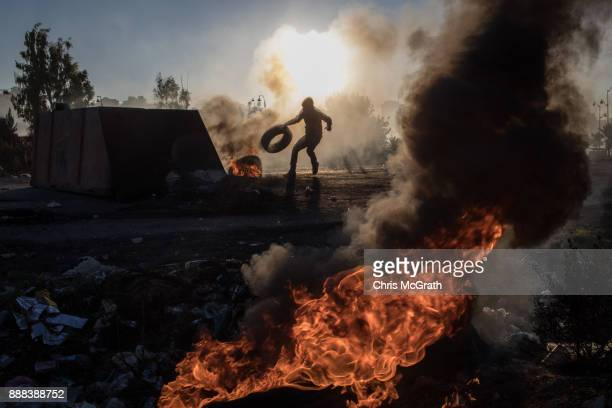 Palestinian protester pushes a tire onto a fire barricade as they clashed with Israeli border guards near an Israeli checkpoint on December 8 2017 in...