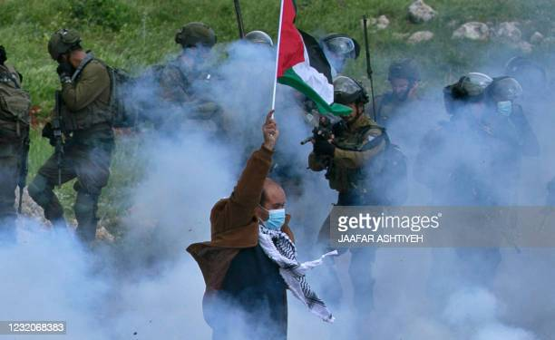 Palestinian protester raises a national flag as a member of the Israeli forces points his gun, amid smoke from tear gas during a demonstration...