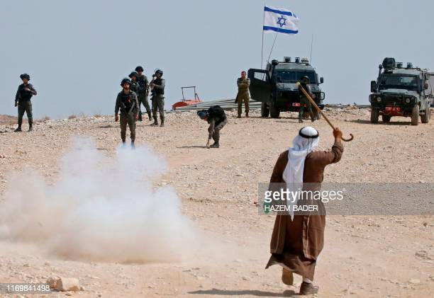 Palestinian protester raises his walking cane as he stands before Israeli border guards during a demonstration against Israeli settlers laying claims...