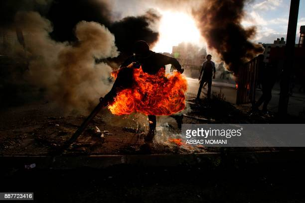 Palestinian protester runs after catching fire during clashes with Israeli troops at a protest against US President Donald Trump's decision to...