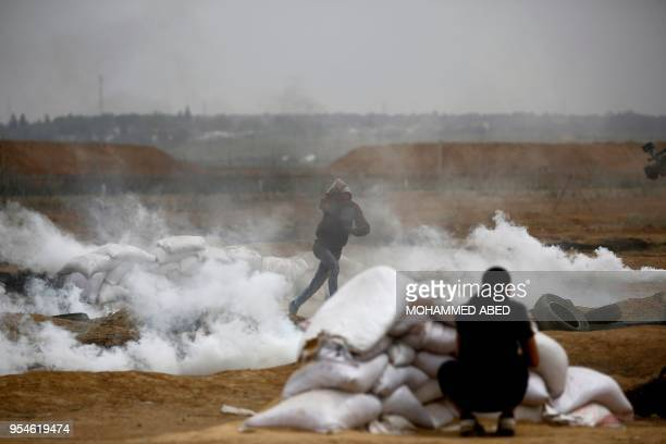 Palestinian protester runs for cover as tear gas canisters fall at the spot of demonstrations near the border fence between Israel and the Gaza...