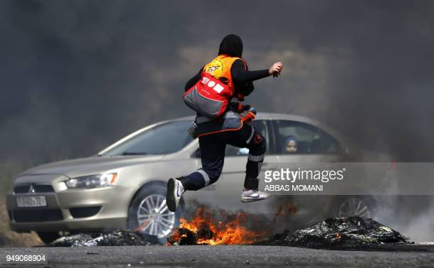 Palestinian protester runs for cover during clashes with Israeli forces following a demonstration near the Israeli settlement of Beit El in the...