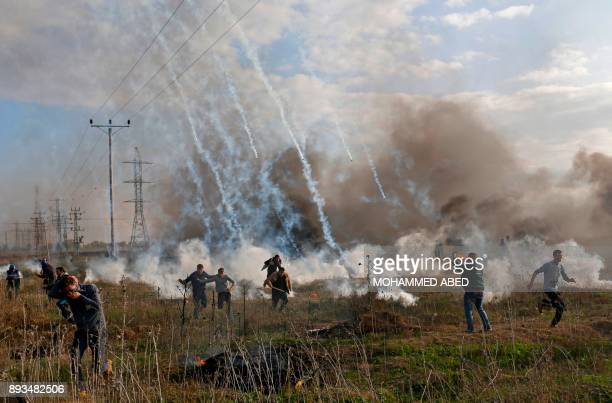 TOPSHOT Palestinian protester runs for cover from tear gas during clashes with Israeli security forces near the border fence with Israel east of Gaza...