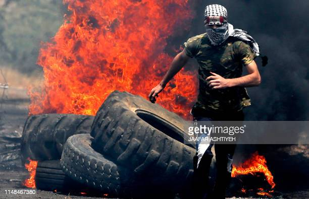 Palestinian protester runs for cover while being chased by Israeli security forces during a weekly demonstration against the expropriation of...