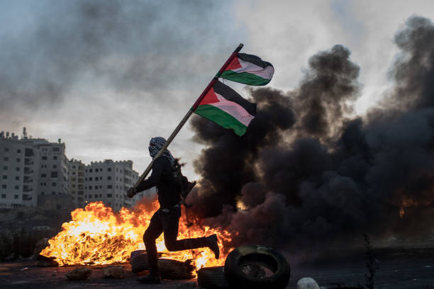 Palestinian protester runs past a burning barricade carrying a Palestinian flag during clashes with Israeli border guards near an Israeli checkpoint...