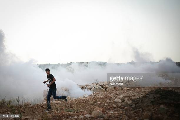 A Palestinian protester runs to seek cover from tear gas fired by Israeli soldiers during clashes in Bil��in near Ramallah West Bank 01 November 2013...