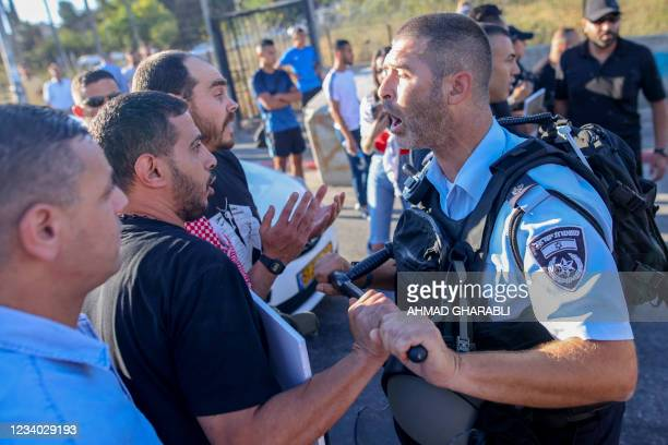 Palestinian protester scuffles with a member of Israeli security forces near an Israeli roadblock at the entrance of the Sheikh Jarrah neighbourhood...
