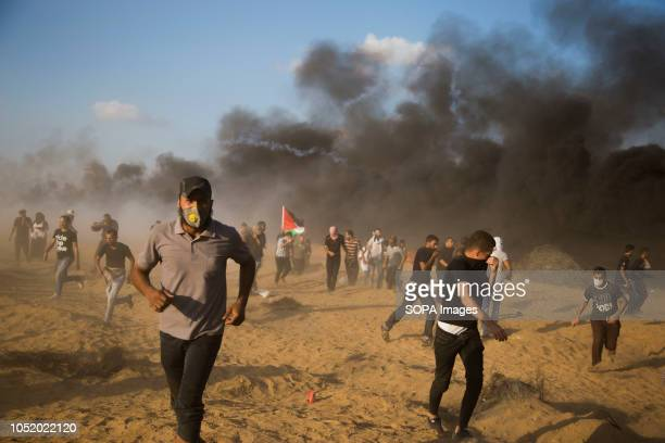 Palestinian protester seen running away from tear gas during the protest Palestinians clash with Israeli forces during a protest calling for lifting...