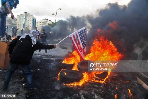 Palestinian protester sets alight an America flag during clashes with Israeli troops at a protest against US President Donald Trump's decision to...