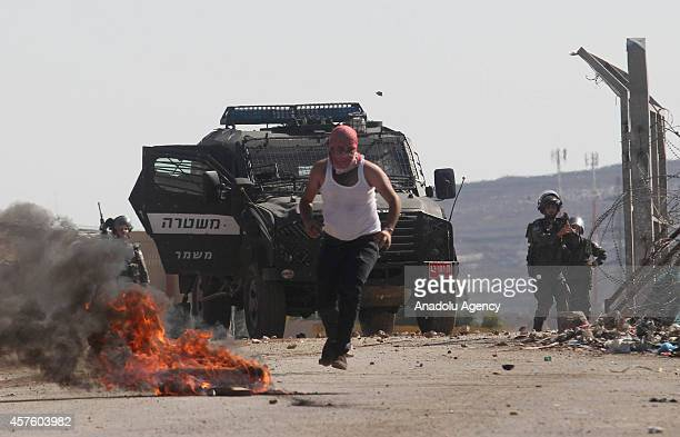 Palestinian protester sets fire to a tire in front of Israeli police vehicle during clashes at the entrance of the Israeli Ofer military prison in...