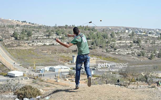 Palestinian protester slingshots a rock at Israeli soldiers during a protest near Ofer prison
