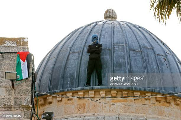 Palestinian protester stands atop Al-Aqsa mosque in Jerusalem on May 10 ahead of a planned march to commemorate Israel's takeover of Jerusalem in the...