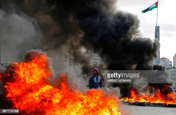 A Palestinian protester stands between burning tyres during clashes with Israeli troops at a protest against US President Donald Trump's decision to...