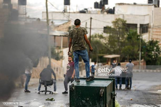A Palestinian protester stands holding stones during clashes with Israeli security forces in the village of Kobar west of Ramallah in the occupied...