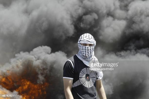 A Palestinian protester stands in front of buring tyres during clashes with Israeli security forces following a weekly demonstration against the...