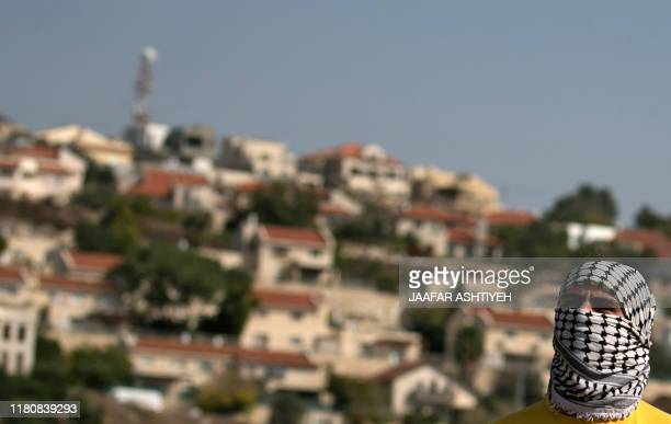A Palestinian protester stands opposite the Jewish settlement of Qadumim amid clashes with the Israeli forces following a weekly demonstration...