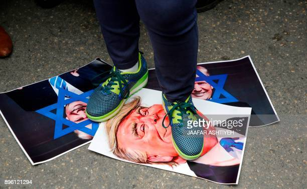 A Palestinian protester stands over cartoons of US President Donald Trump and pictures of him defaced with a blue Star of David during a...
