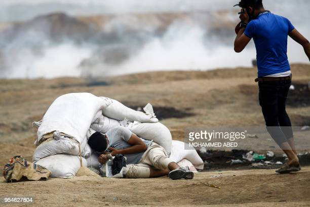 Palestinian protester takes cover behind sandbags during clashes with Israeli forces along the border with the Gaza strip east of Jabalia on May 4 on...