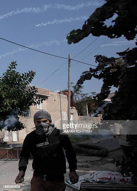 A Palestinian protester takes cover from tear gas fired by Israeli soldiers during clashes in the northern West Bank village of Kfar Qaddum on...