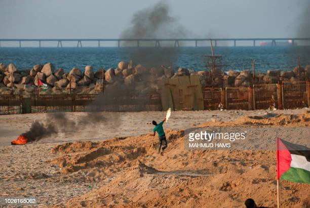 Palestinian protester throws a molotov cocktail across on a beach along the Gaza sea barrier on the border with Israel near Kibbutz Zikim north of...