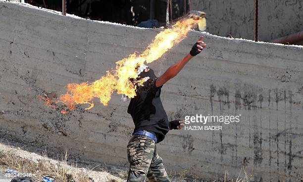 A Palestinian protester throws a Molotov cocktail towards Israeli security forces during clashes in the village of Beit Omar near the city of Hebron...