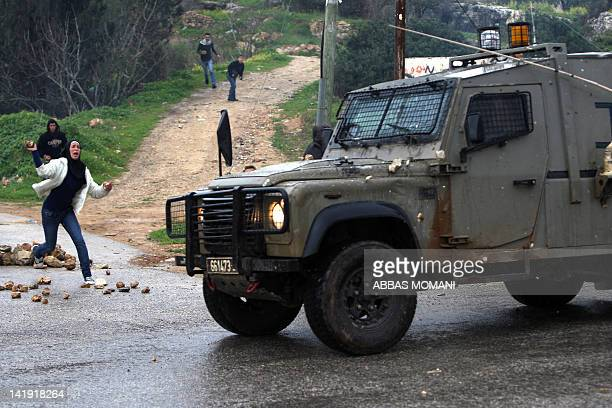 A Palestinian protester throws a stone towards an Israeli military vehicle during a weekly demonstration in the West Bank village of Nabi Saleh...