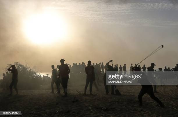 Palestinian protester throws a stone towards Israeli forces during a demonstration on the beach near the maritime border with Israel in the northern...