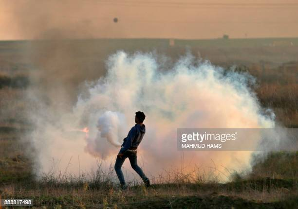 A Palestinian protester throws a tear gas canister back at Israeli forces during clashes near the IsraelGaza border east of Gaza City on December 9...