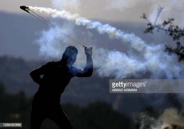 Palestinian protester throws a tear gas canister towards Israeli soldiers who fired it during a demonstration against Israeli land seizures for...