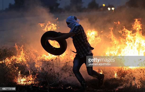 A Palestinian protester throws a tire into a fire during clashes with Israeli security forces following a protest in reaction to the death of the...