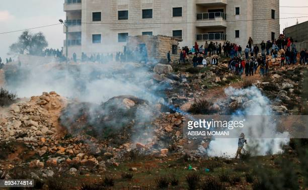 Palestinian protester throws back a tear gas canister back during clashes with Israeli forces near an Israeli checkpoint in the West Bank city of...