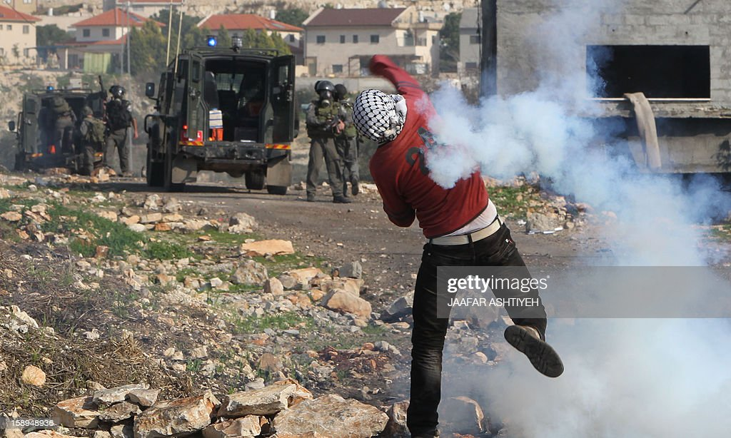 A Palestinian protester throws back a tear gas canister fired by Israeli soldiers during a demonstration against the expropriation of Palestinian land by Israel in the village of Kfar Qaddum, near the occupied West Bank city of Nablus, on January 4, 2013.