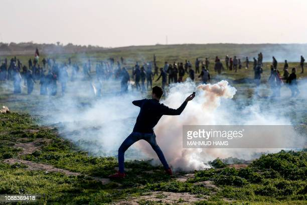 A Palestinian protester throws back a tear gas canister towards Israeli forces during clashes following a demonstration along the border with Israel...
