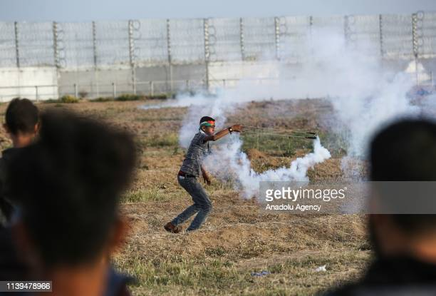 "Palestinian protester throws back a tear gas canister with a slingshot to Israeli forces during a protest within the ""Great March of Return"" at..."